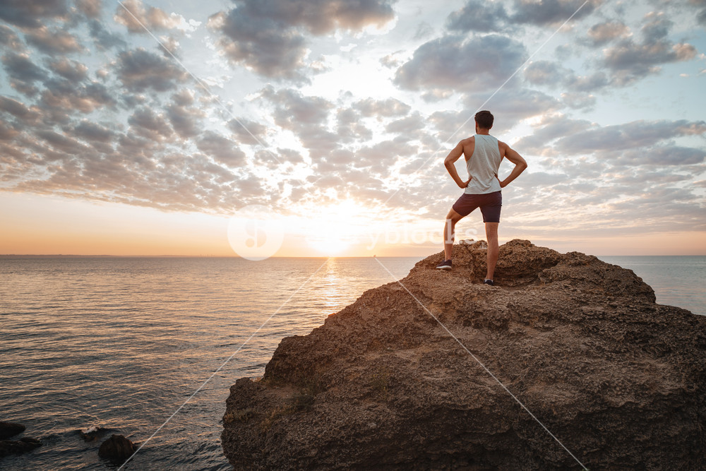 Young sportsman standing backwards on the mountain rock by the sea and looking at sunset