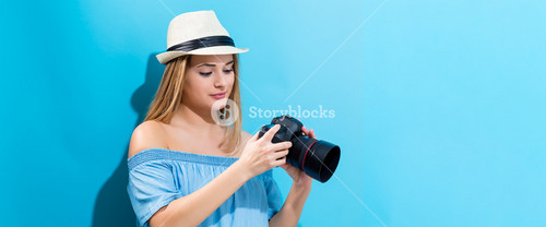 Young woman holding a camera on a blue background