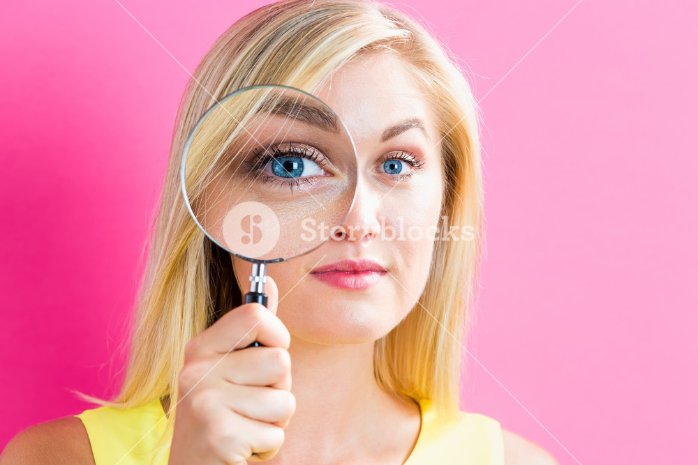 Young woman looking through a magnifying glass on a pink background