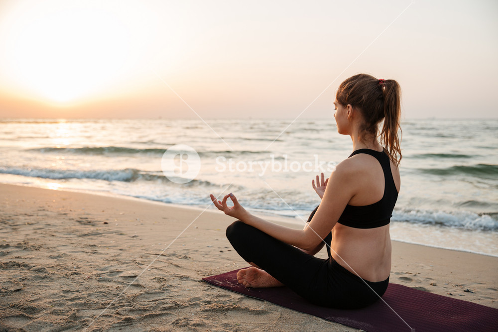 Young woman meditating on the beach at sunset