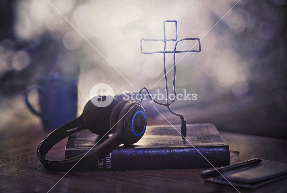 Headphones attached to a Bible with a cross shape