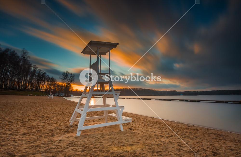 Lake landscape with lifeguard hut. Long exposure photo with dramatic sky. Polish lake beach on Mazury lake district.