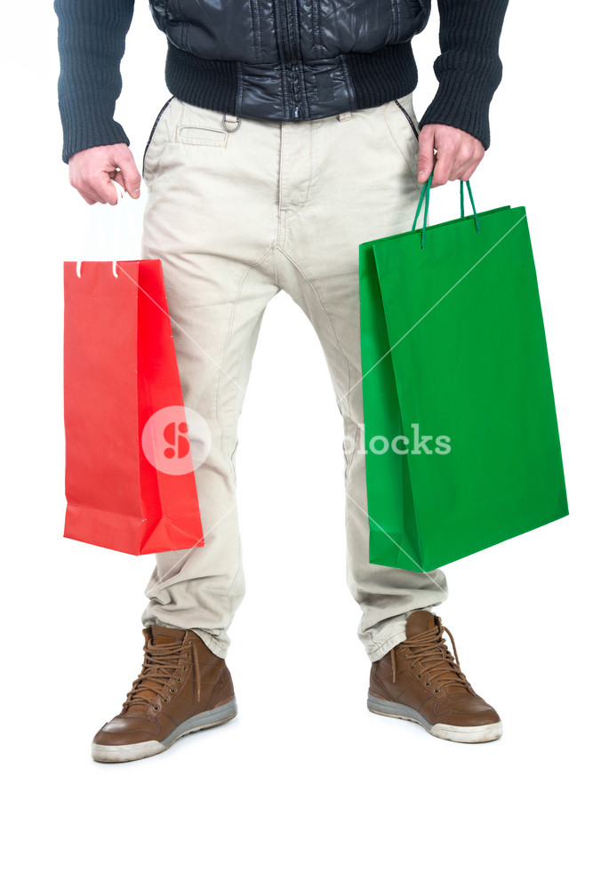 Lower part of man holding shopping bags isolated on white