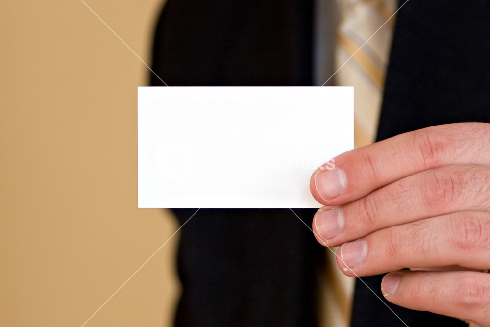 Macro shot of a man holding a business card up.  Plenty of copyspace for your logo or design.