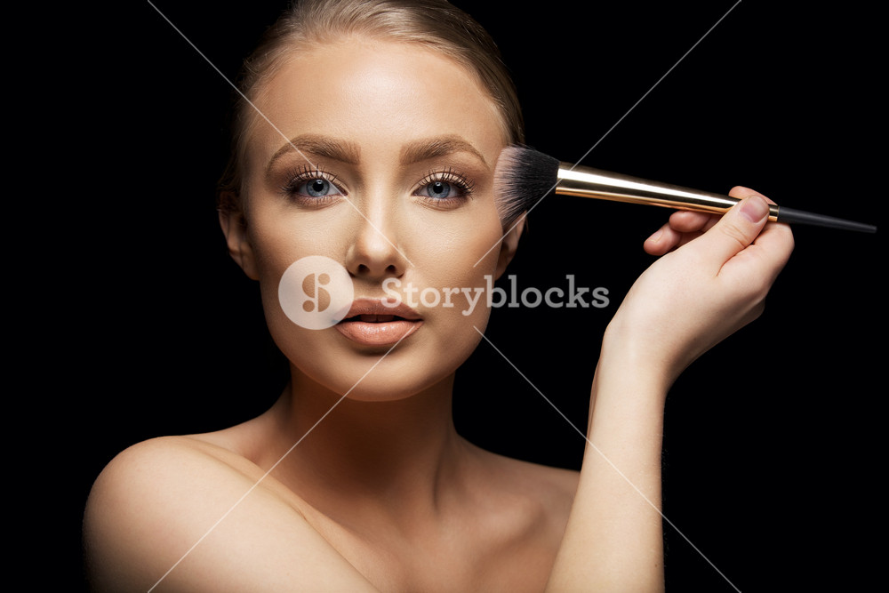 Makeup applied by beautiful young woman. Model brushing foundation on her soft skin. Beautiful caucasian fashion model on black background.