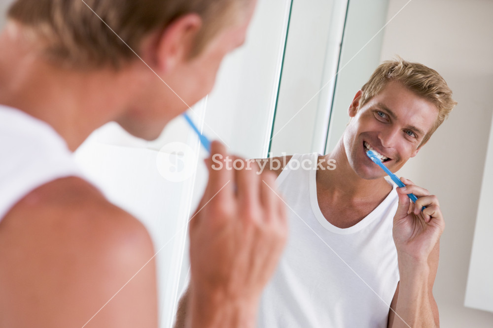 Man in bathroom brushing teeth and smiling