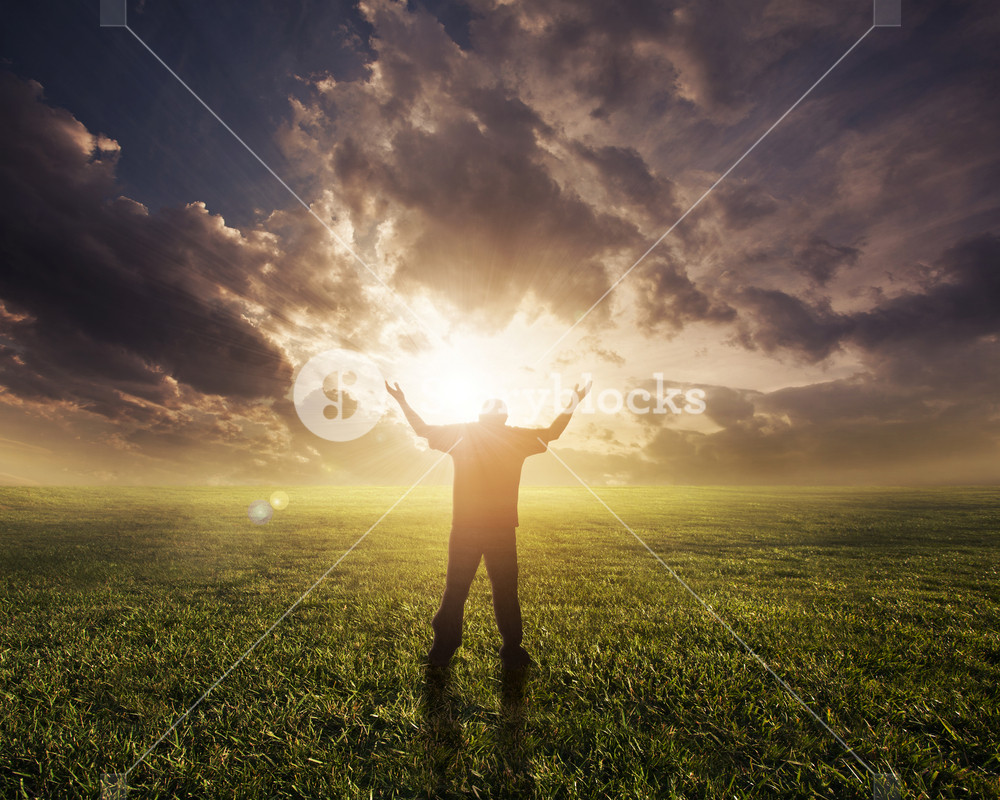 Man lifting hands in worship at sunset.