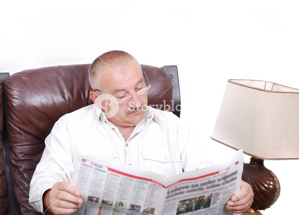 Middle aged man is sitting and reading newspapers