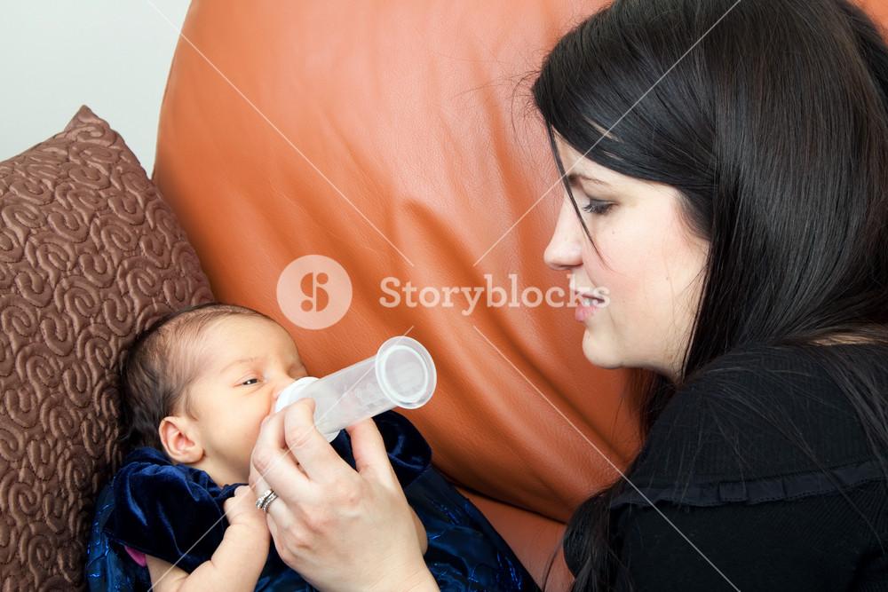 Mother feeds her newborn infant feeds on a bottle of baby formula.