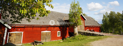 old red farm in rural landscape