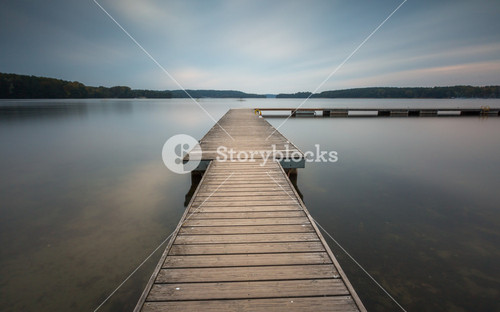 Panoramic landscape with wooden jetty on city beach of Olsztyn in Poland. Long exposure landscape with architecture elements.