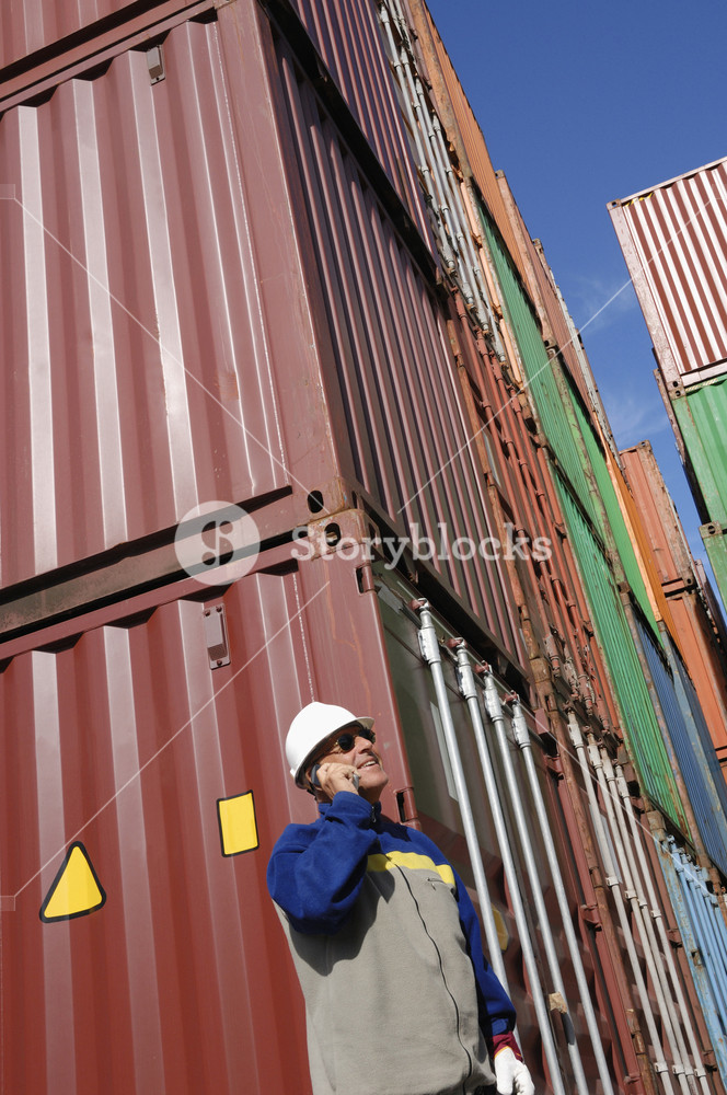 port worker with stacks of shipping containers in background