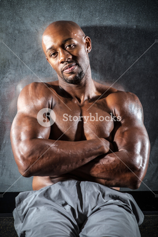 Portrait of a lean toned and ripped muscle fitness man under dramatic low key lighting.