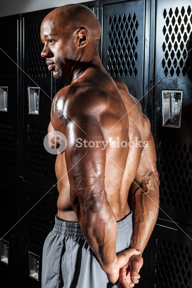 Portrait of a muscle fitness mans back and shoulders in the locker room.