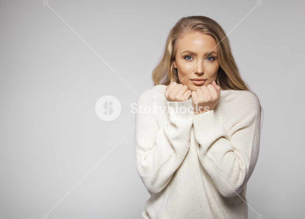 Portrait of beautiful young blonde wearing sweater feeling cold. Cute young female fashion model posing on grey background with copyspace.