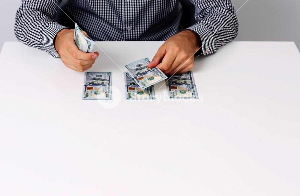 Portrait of businessman counting hundred dollar bills at desk