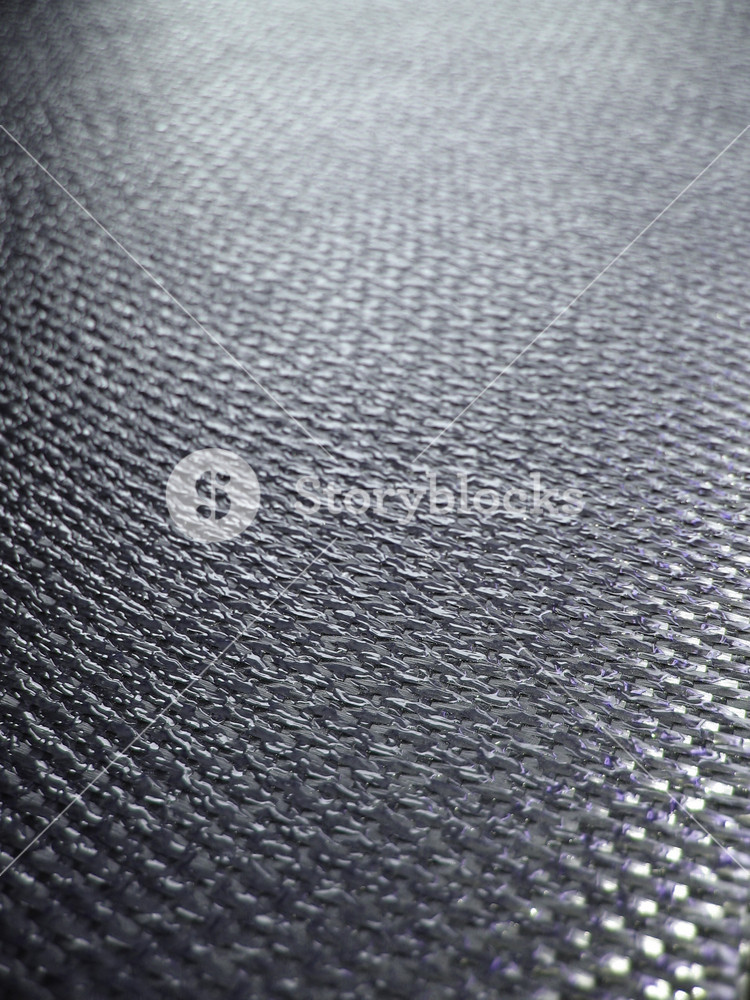 Real carbon fiber in its raw form - this material is used to make durable and strong parts for cars, boats, bikes, and even photography equipment. Shallow depth of field.