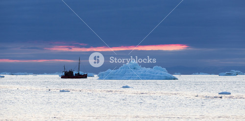 Red boat traveling past an iceberg at sunset