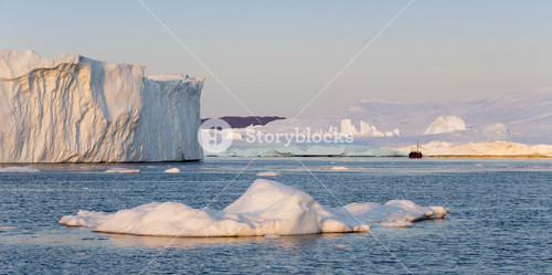 Red boat traveling past sunlit icebergs and ice floe