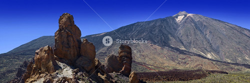 Rock formation and a mountain under a blue sky