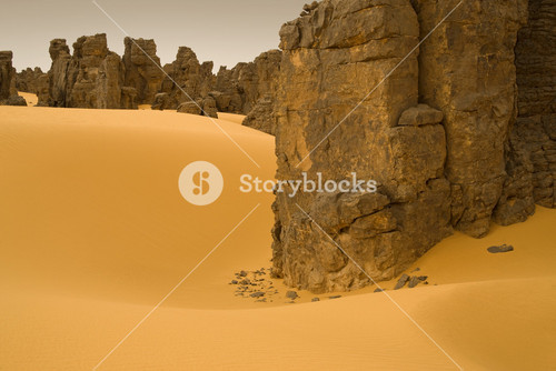 Rock formations in a sandy desert at dusk
