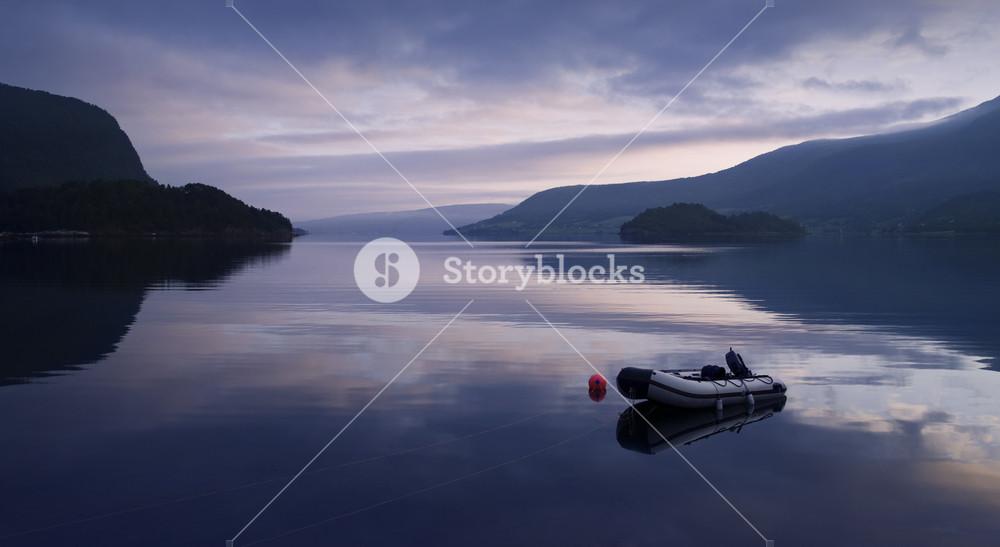 Rowboat on a still lake at sunset