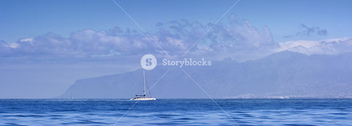 Sailboat in bright blue water along the coast