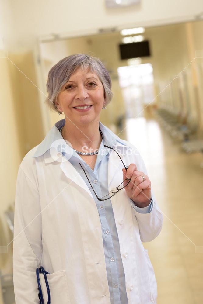 Senior doctor standing in hospital corridor smiling