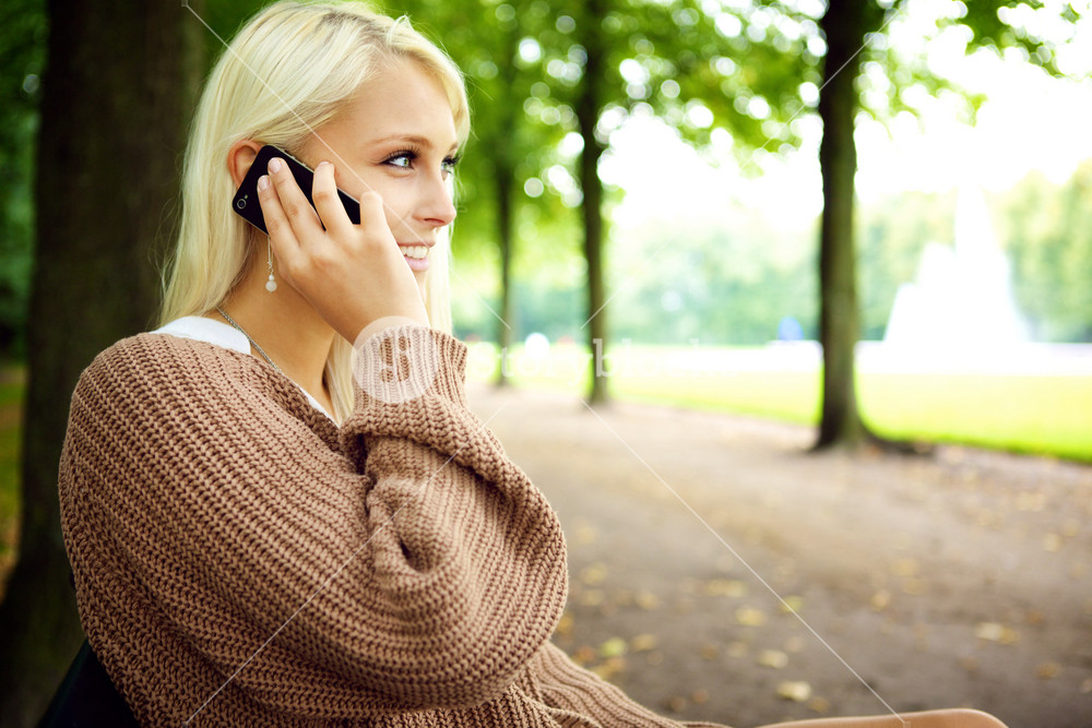 Sexy sensual blonde female model In animated conversation on her mobile phone in the park.
