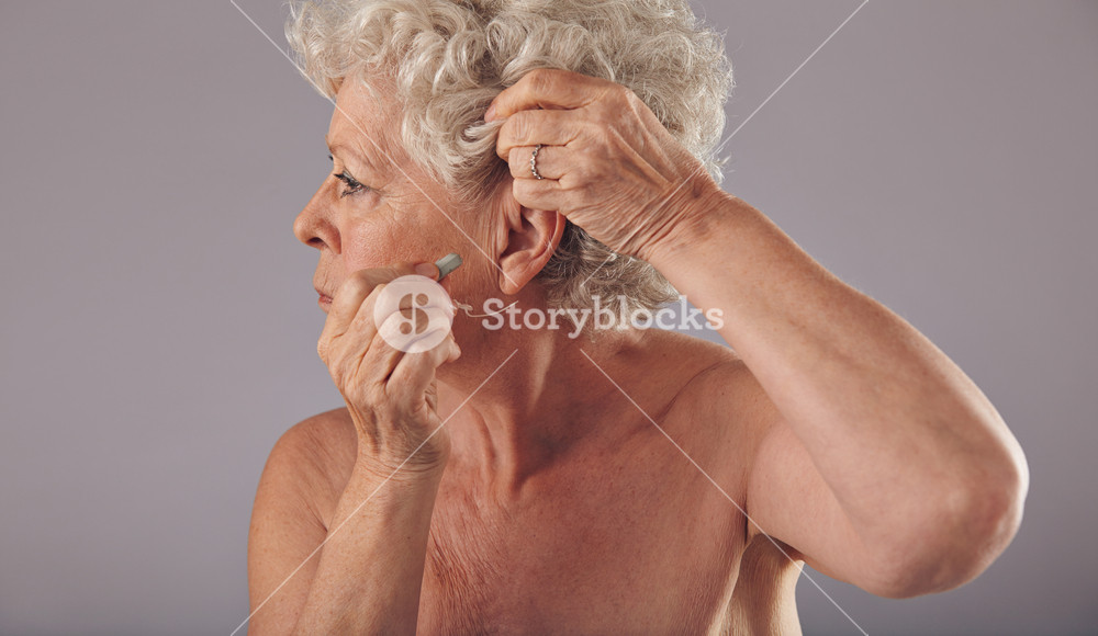 Side view portrait of a senior woman inserting a hearing aid in her ear against grey background. Modern hearing aid for old people.