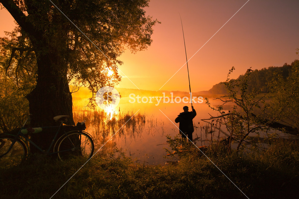 Silhouette of fisherman with fishing rod on the lake at sunset