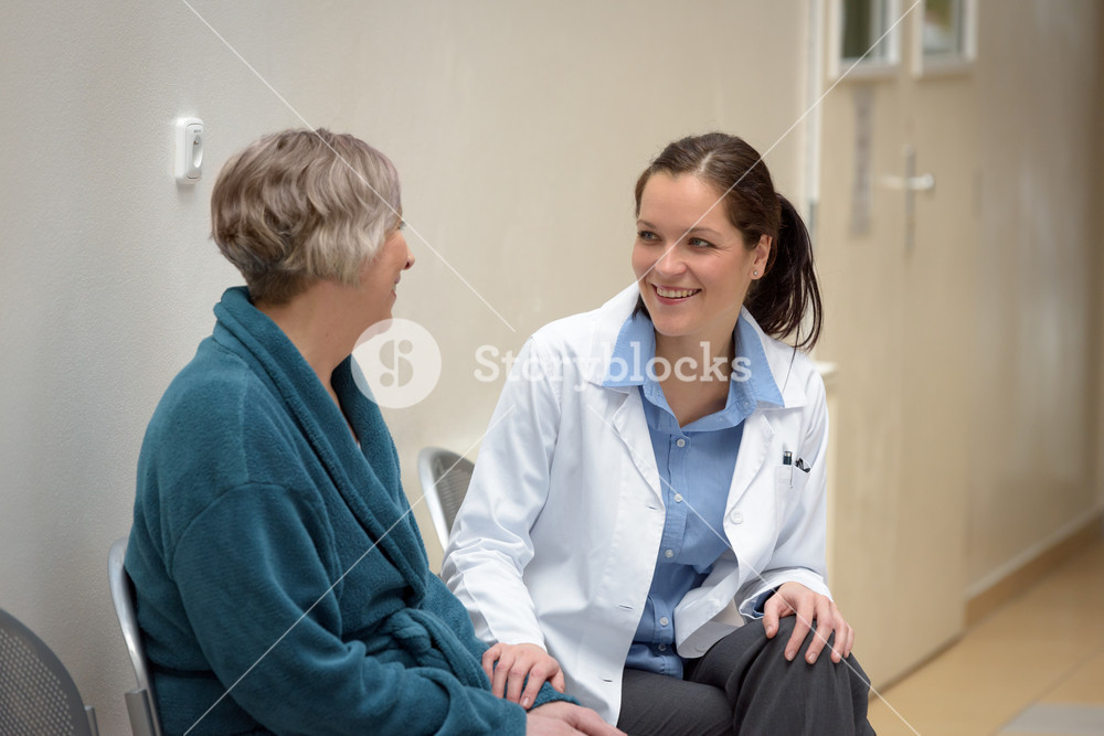 Smiling female doctor talking to senior patient in hospital