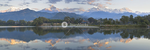 Snow-capped mountain range reflected in a lake at sunrise