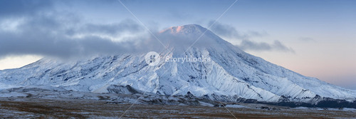 Snowy mountain under thick clouds at dawn