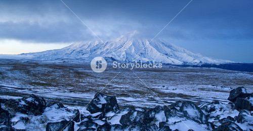 Snowy mountain under thick storm clouds