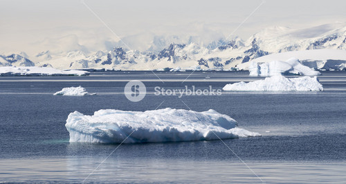 Snowy, rocky coast and sunlit icebergs under a cloudy sky