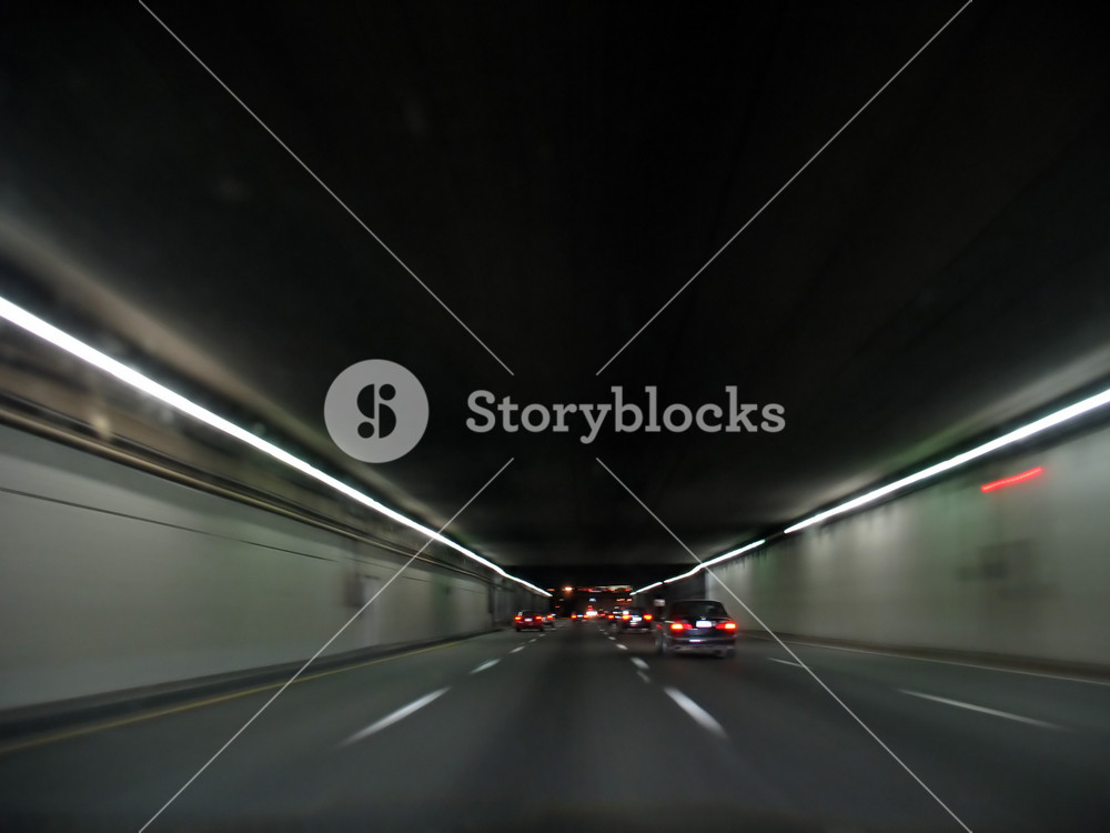 Speeding down the highway through a tunnel at night time.