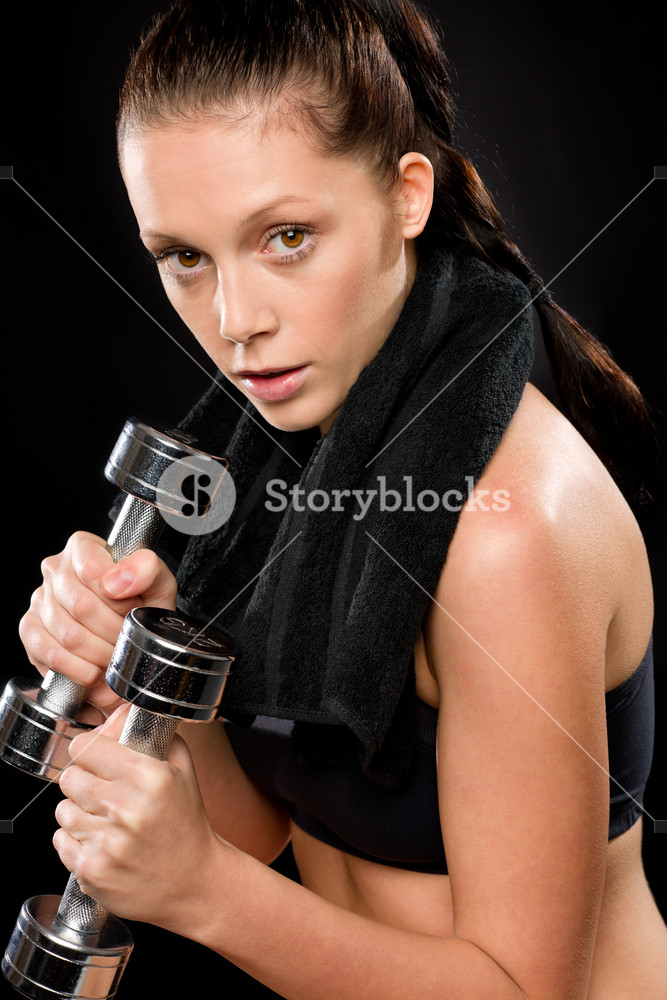Sporty young woman exercising lifting weights with towel behind neck