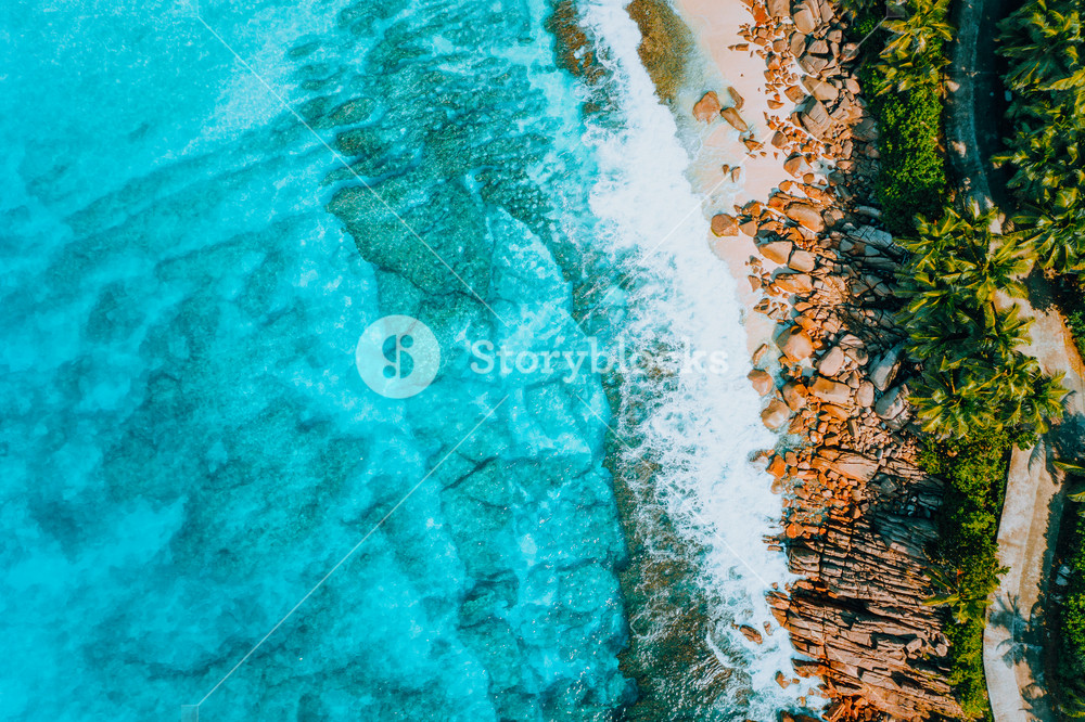 Aerial bird eye shot of tropical coastline with tropical rocky beach and palm trees at Seychelles. Summer vacation, travel and lifestyle concept