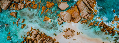 Aerial top panorama view of ocean shore huge bizarre granite rocks boulders on tropical beach with turquoise azure water. Amazing rock cliff seascape and coastline Seychelles La Digue Island