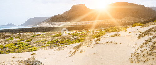 Amazing sunset over volcanic mountains on desolated atlantic coast. Sunrays falling on coastal dunes Sao Vicente Cape Verde