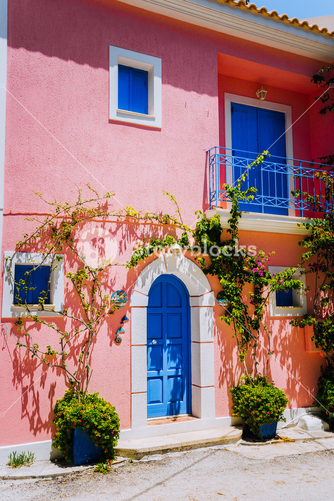 Assos village. Traditional pink colored greek house with bright blue door and windows. Fucsie plant flowers arount entrance welcome gate. Kefalonia island, Greece
