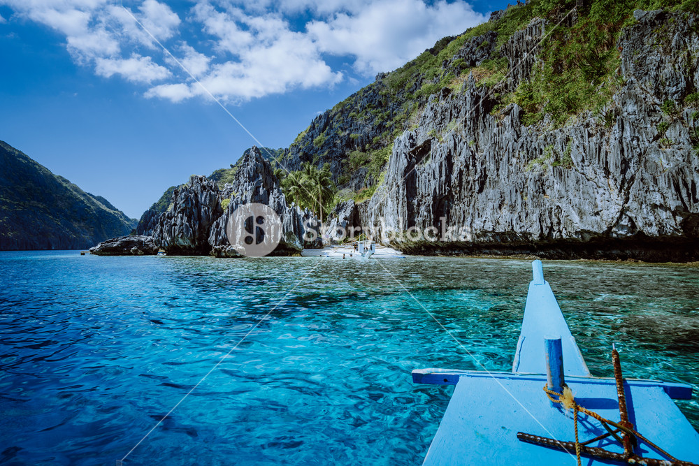 Banca boat approaching small beach at the Shrine, on Matinloc island, highlights of hopping trip Tour C. Must see, most beautiful place at Marine National Park, Palawan