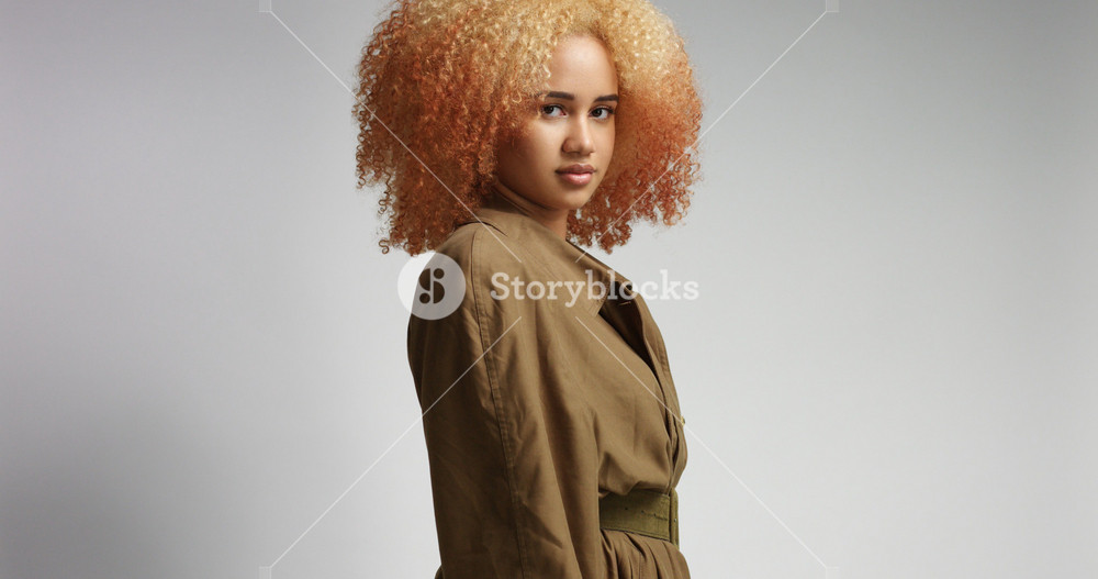 Beautiful strong confident black model in khaki thin coat isolated on white
