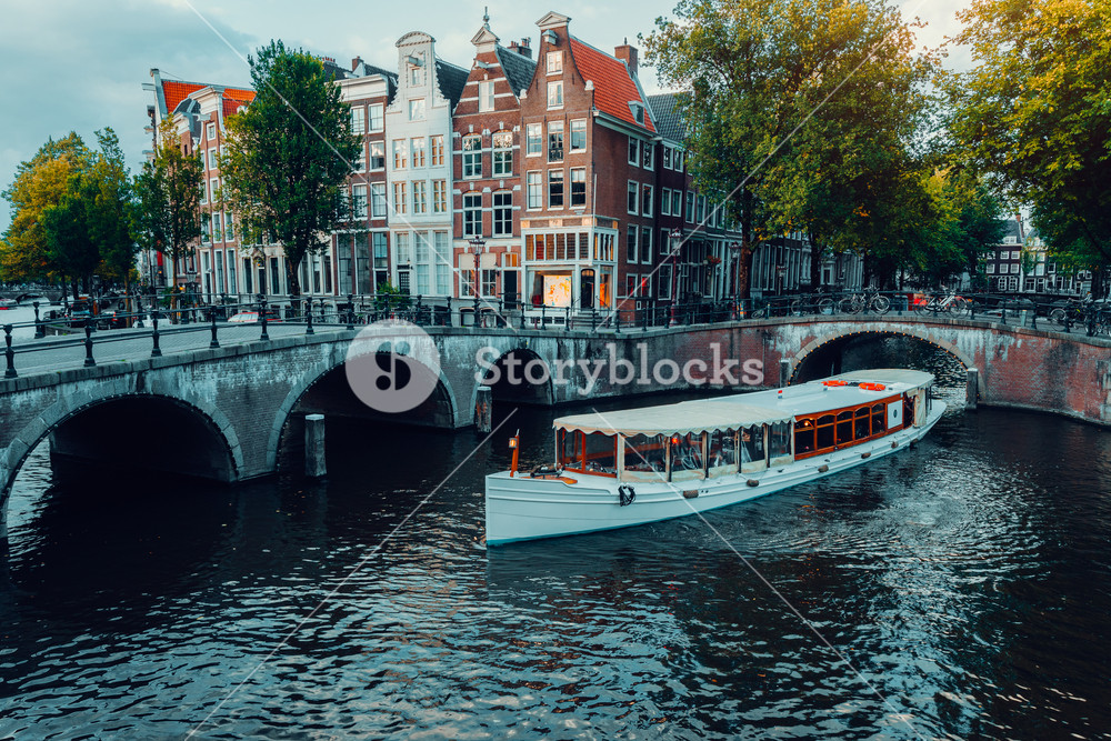 Beautiful view of Amsterdam canals with white cruise boat bridge and typical dutch houses. Holland