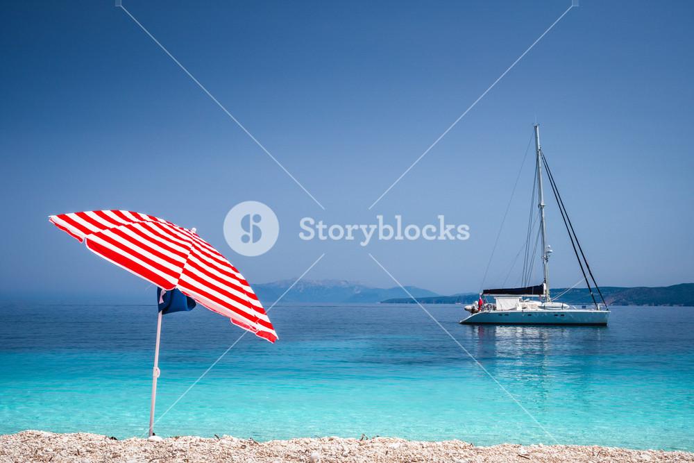 Bright red striped sun beach umbrella on pebble beach against turquoise blue shellow sea water and clean blue sky. White catamaran sailing boat drift in calm blue sea water surface