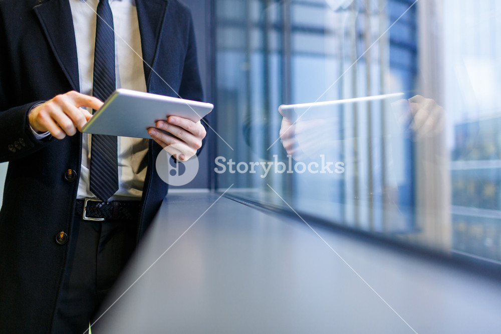 Businessman with touchpad networking by window