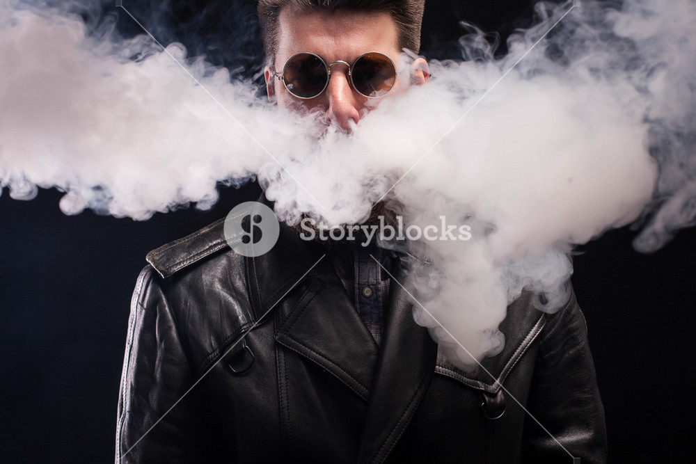Cigarette smoking coming out of handsome bearded man nose over black background.