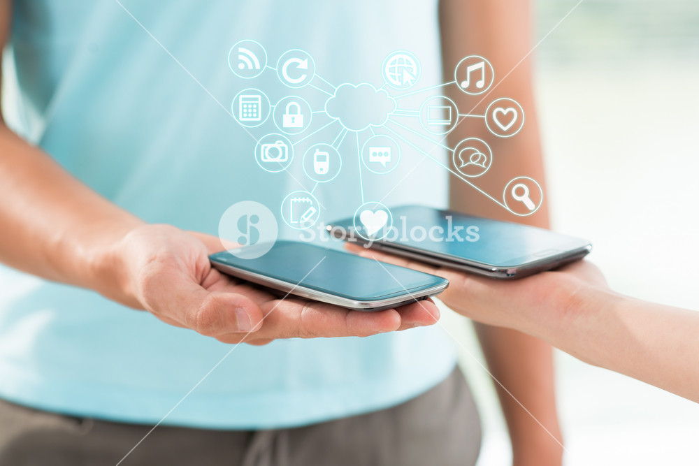 Close up image of human hands holding modern multifunctional smartphones on the foreground
