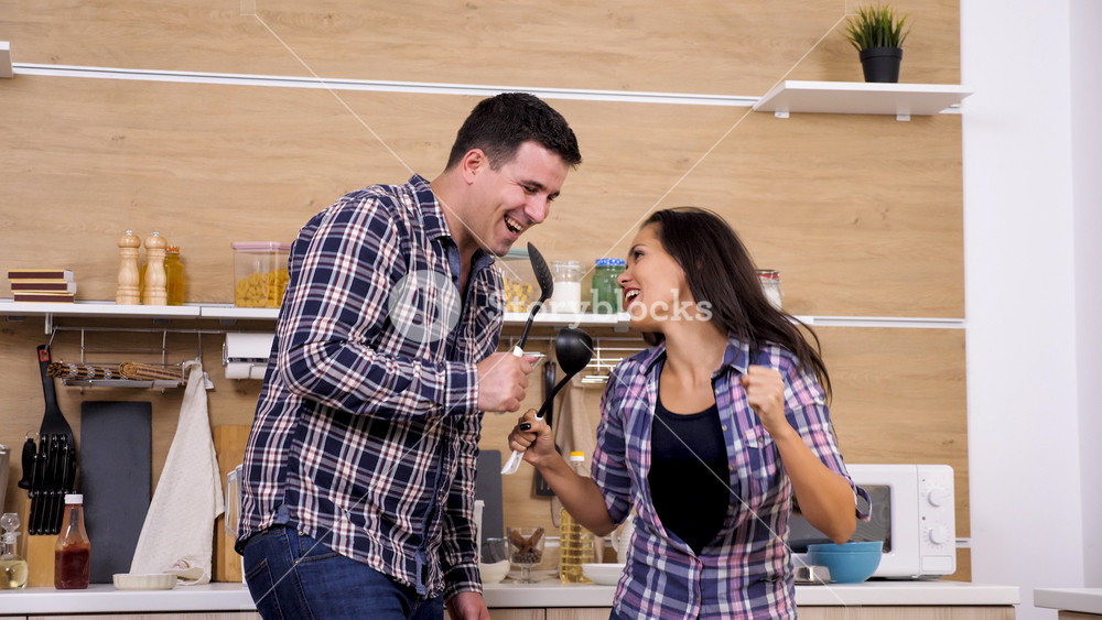 Couple singing in thier kitchen and telling stories. Sweet moment.